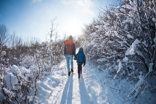 A child with a backpack walks with mother in a snowy forest