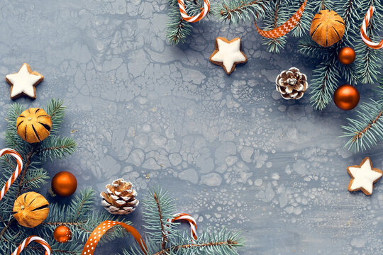 Grey textured Zero Waste Christmas background. Xmas flat lay, top view arrangement of natural fir twigs, dry oranges, stripy candy canes, pine cones and orange baubles. Toned image.