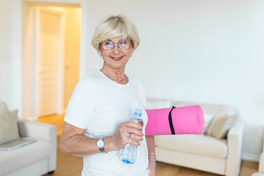 Mature Woman getting ready for a workout. Elderly woman ready for working out. Refreshment after training. Sporty old woman drinking water