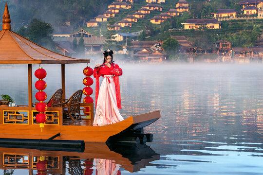 Asian woman wearing chinese traditional dress on Yunan boat at Ban rak thai village in mae hong son province, Thailand.