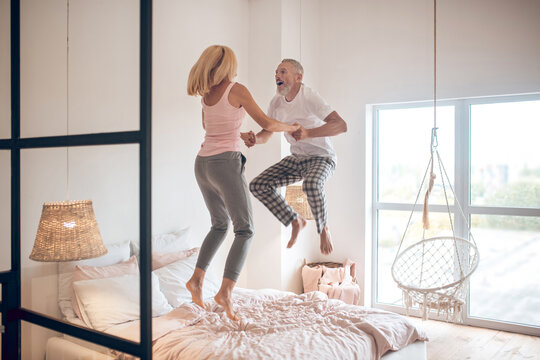 Mature couple jumping on the bed and feeling awesome