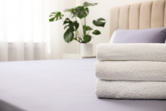 Stack of clean towels on bed indoors, closeup. Space for text