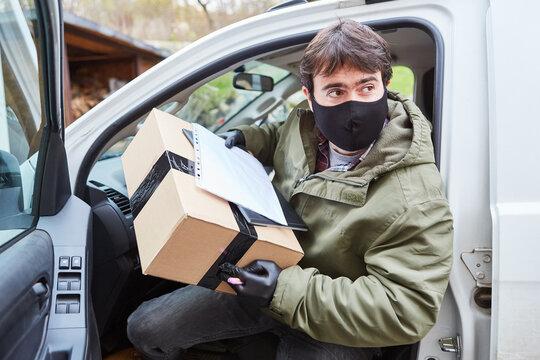 Paketbote mit Mundschutz verlässt sein Fahrzeug