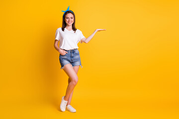 Full size photo of fit brown haired woman show empty space wear white t-shirt blue pin-up isolated on yellow color background Wall mural