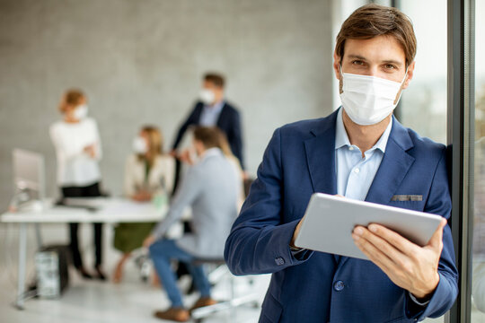 Handsome young business man wearing protective facial mask while holdind digital tablet