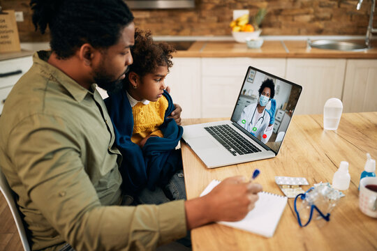 African American father and daughter having video call with family doctor due to coronavirus pandemic.
