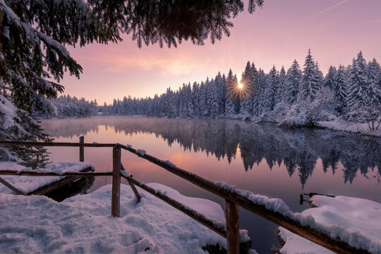 Scenic winter landscape of calm lake with wooden pier covered with snow and coniferous forest reflected in water in sunset time