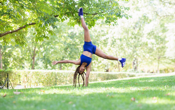 Upside down view of flexible ethnic female athlete in sportswear performing cartwheel on green lawn in park during training