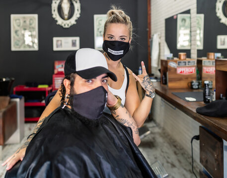 Young tattooed female barber in protective mask with Fuck Corona text standing near hipster male client and showing rock sign during work in modern barbershop