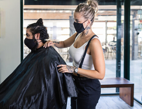 Young tattooed female barber in protective mask standing near hipster male client during work in modern barbershop