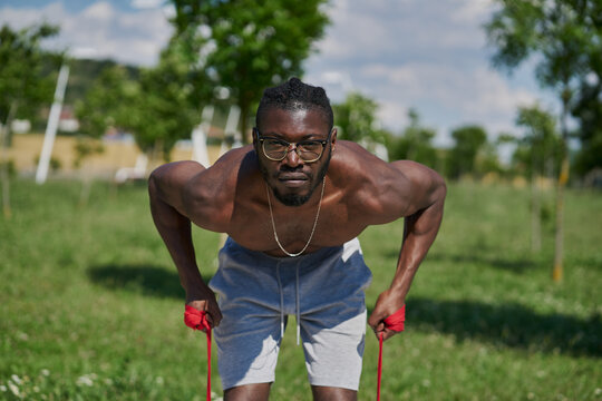 Strong active African American male with naked muscular torso doing resistance bend bicep curl exercise during functional workout on street