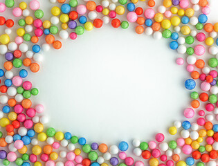 Colorful bright candy on a white background spread out in the form of a wreath frame. Top view of small balls with copy space for text