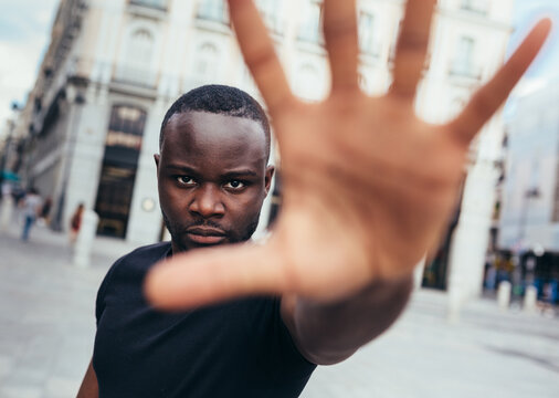 Man protesting at a rally for racial equality raising arms showing hand to camera. Black Lives Matter.