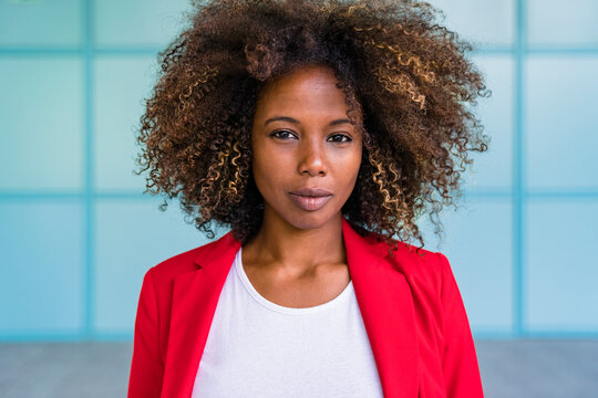 Woman with curly hair standing against wall