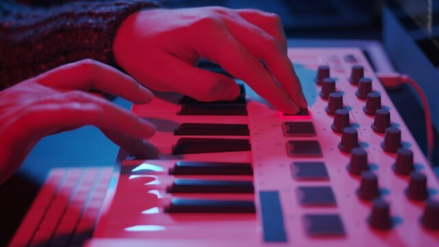 Closeup of hands composing music in night using midi controller. Playing beat music with electronic keyboard, midi keys on the table with neon lights