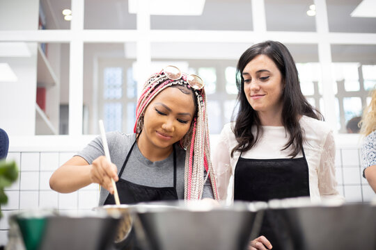 Content multi ethnic women stirring dish in pot at cooking workshop