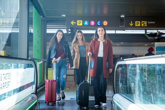 Glad friends with suitcase walking fast by walkway in airport