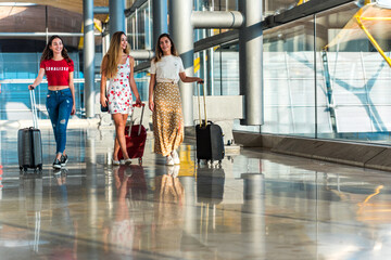Stylish women with suitcases walking in airport Fotobehang