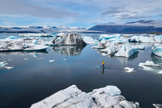 Man stand up paddle boarding through glacier lagoon in Iceland