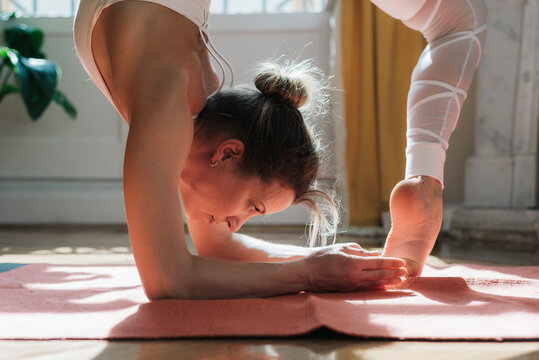 Woman in Scorpion pose doing yoga at home