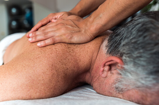 Woman massaging back of elderly patient