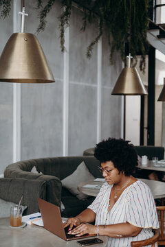 Plump black woman using laptop in cafe