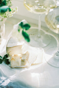 bouquet of white flowers in a vase, two wineglasses and goat cheese