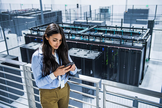 Mixed race businesswoman using cell phone on balcony over server room