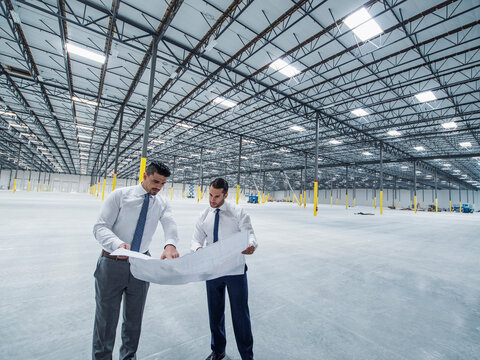 Architects examining blueprint in empty warehouse