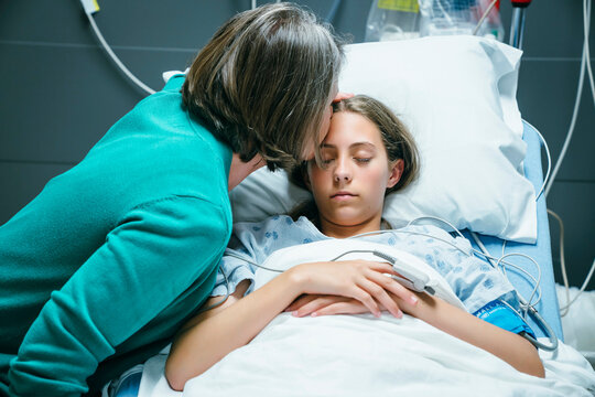 Caucasian mother kissing your daughter on forehead in hospital