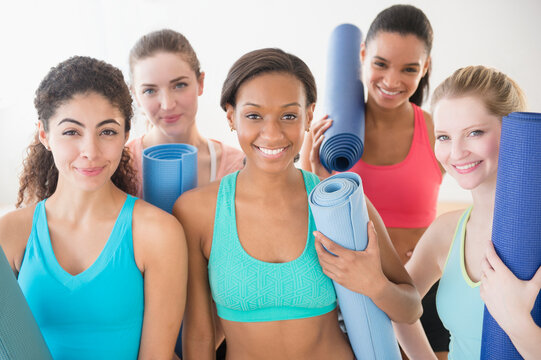 Women smiling together with exercise mats