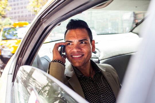 Hispanic businessman talking on cell phone in back seat of car