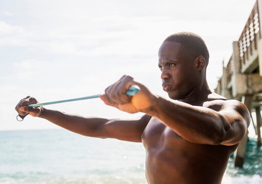 Mixed race man using resistance band on beach