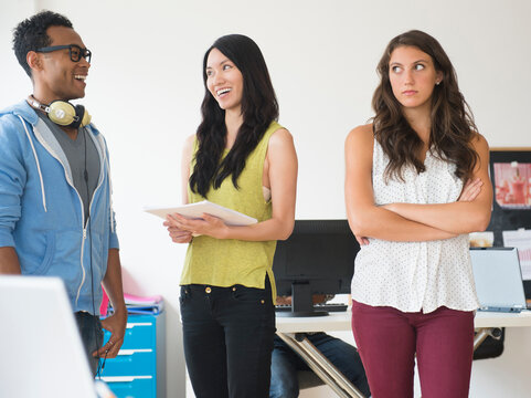 Annoyed businesswoman ignoring colleagues in office