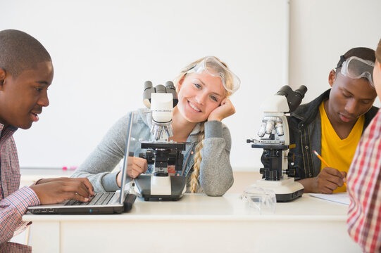 Teenage students using microscopes in science laboratory