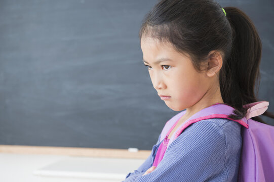 Frowning Vietnamese girl standing in classroom