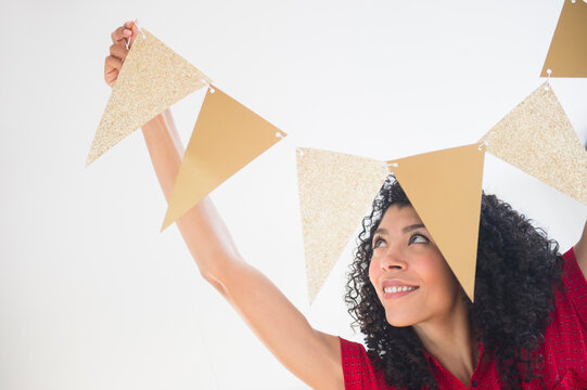 Mixed race woman hanging celebration banner
