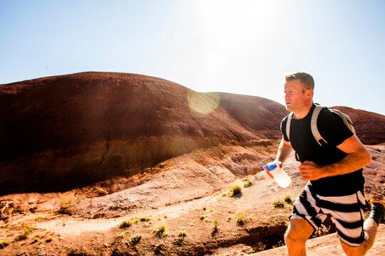 Caucasian man running in desert hills