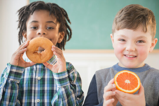 Students eating donut and orange in classroom