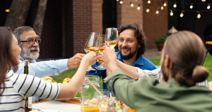 Happy Caucasian family sitting at table in dinner at home back yard and toasting with drinks. Cheerful males and females people saying toasts with glasses in hands.