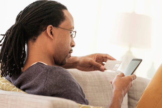 Black man shopping with cell phone on sofa