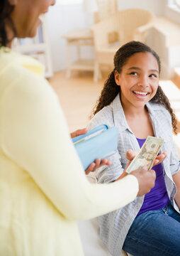 Mother handing money to daughter