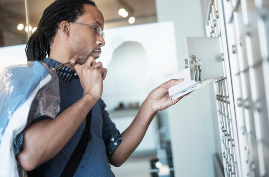 Black man gathering mail from post office box