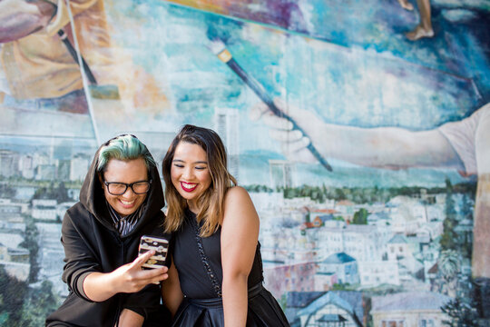 Smiling Asian women posing for cell phone selfie