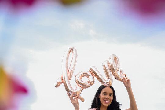 Hispanic woman holding love balloon outdoors