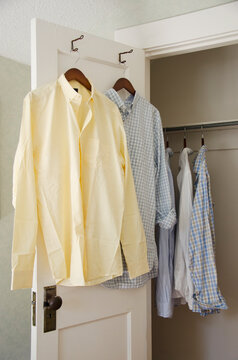 Button down shirts hanging on cloth hangers