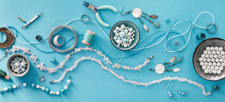 Creative flat lay, panoramic composition. DIY craft hobby. Making handmade jewelry for friends as Christmas gifts. Flat lay on mint color background.