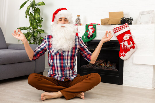 Santa Claus sits and meditates against the fireplace