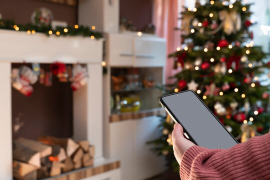 In the apartment at Christmas time, a woman holds a smartphone. In the foreground is the mobile with Copy Space. In the background is Bokeh from the Christmas tree.