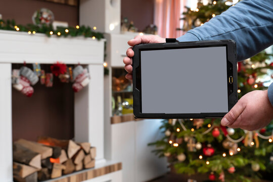 In the apartment at Christmas time a man is holding a tray. In the foreground is the Tablet PC with Copy Space. In the background is Bokeh from the Christmas tree.